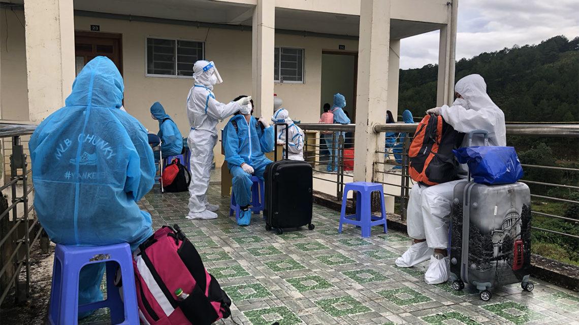 Người mặc đồ bảo hộ chờ xét nghiệm tại khu cách ly ký túc xá trường cao đẳng du lịch